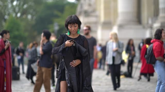 a guest wears green earrings a black lace mesh dress green shoes a belt outside margiela during paris fashion week womenswear spring/summer 2018 on... - örhänge bildbanksvideor och videomaterial från bakom kulisserna