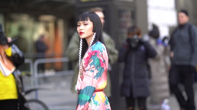 a guest wears multi color flower print dress long white earrings silver shiny shoes a black cylinder shaped bag with chinese print during london... - london fashion week stock videos and b-roll footage