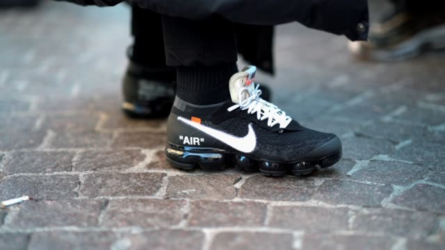 guest wears nike sneakers shoes with white shoe lace, during milan menswear fashion week fall/winter 2018/19 on january 14, 2018 in milan, italy . - scarpe da ginnastica video stock e b–roll