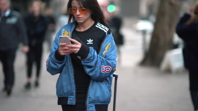 A guest wears orange clear sunglasses a Diesel bomber jacket with an eagle printed logo WILD SPIRIT an Adidas top during London Fashion Week Men's...