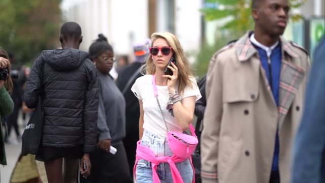 a guest wears pink sunglasses a white tshirt a pink fanny pack bag denim pants outside paco rabanne during paris fashion week womenswear spring... - pink shirt stock videos and b-roll footage