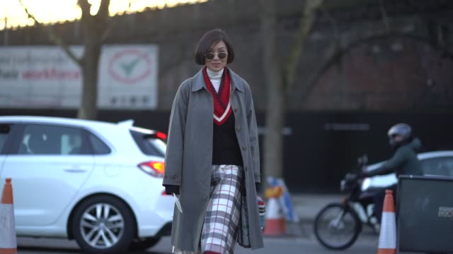 stockvideo's en b-roll-footage met a guest wears red boots a gray coat a checked skirt a white turtleneck during london fashion week february 2018 on february 17 2018 in london england - coltrui