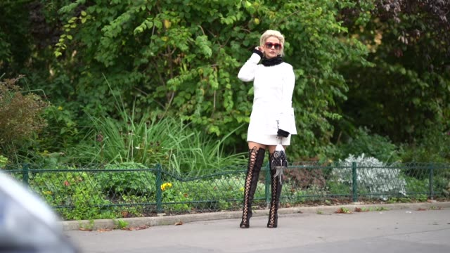 A guest wears red sunglasses a white dress black thigh high leather boots a Chanel rocket shaped bag outside Moncler during Paris Fashion Week...