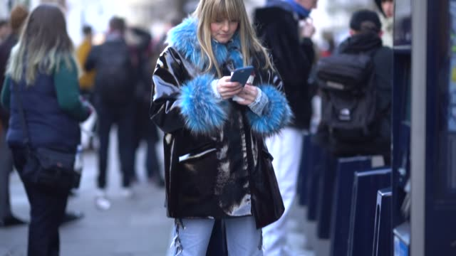 guest wears silver shoes, blue jeans, a black shiny coat with blue fur lining, and is using a smartphone, during london fashion week men's january... - london fashion week点の映像素材/bロール