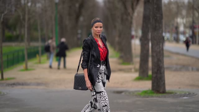 guest wears strass earrings, a black headband, a black jacket, a chanel black bag, a red and black shirt, a black print white crop pants, peep-toe... - kosmetisches stirnband stock-videos und b-roll-filmmaterial