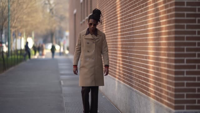 guest wears sunglasses, a beige long double breasted coat with buttons, brown pants, leather shoes, outside fendi, during milan fashion week menswear... - milan fashion week stock videos & royalty-free footage