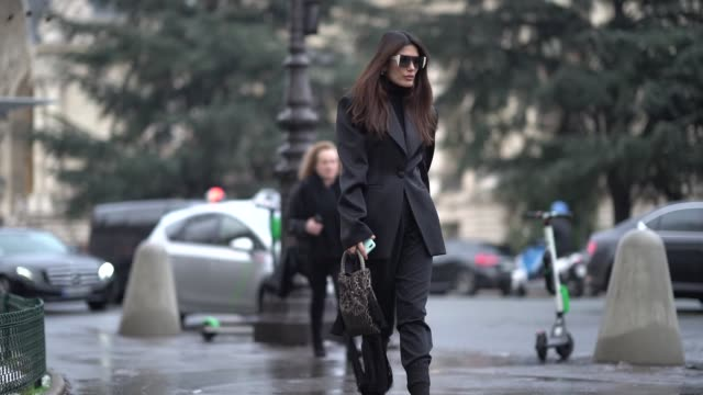 A guest wears sunglasses a black blazer jacket a bag black boots with heels outside Alexandre Vauthier during Paris Fashion Week Haute Couture Spring...