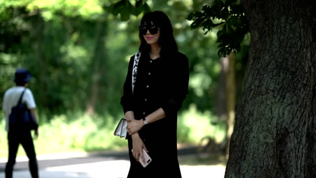 guest wears sunglasses, a black dress, and flower print shoes, outside the balenciaga show, during paris fashion week - menswear spring/summer 2018,... - black dress stock videos & royalty-free footage
