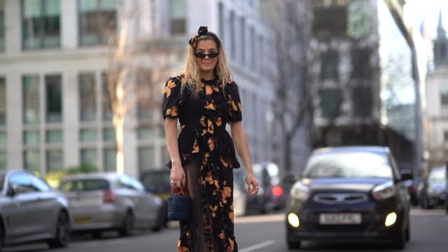 vídeos de stock e filmes b-roll de guest wears sunglasses, a black dress with yellow flower print, during london fashion week february 2018 on february 17, 2018 in london, england. - vestido preto