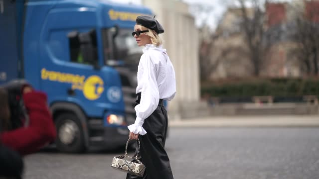vídeos de stock e filmes b-roll de a guest wears sunglasses a black leather dior beret hat a white victorian top black leather wideleg cuffed pants with a bow belt a beige python... - sandália