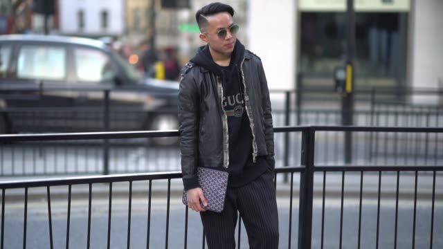 A guest wears sunglasses a black leather jacket a clutch a black hoodie during London Fashion Week Men's January 2018 on January 07 2018 in London...