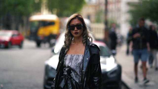 a guest wears sunglasses a black pvc coat a snake print top a black skirt black shiny shoes during london fashion week september 2018 on september 14... - pvc stock videos and b-roll footage