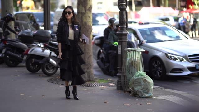 A guest wears sunglasses a black ruffle skirt a black bomber jacket black leather shoes outside Acne Studios during Paris Fashion Week Womenswear...
