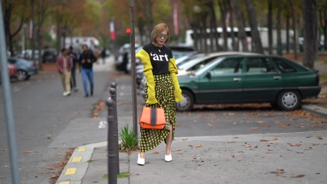 A guest wears sunglasses a black top a yellow cardigan a gathered on one side yellow and black checked skirt an orange and dark brown bag white shoes...