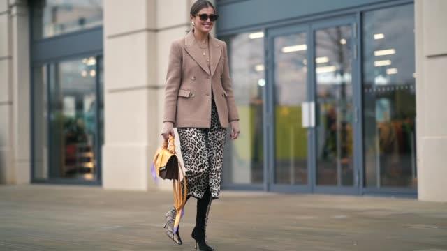 vidéos et rushes de guest wears sunglasses, a blazer jacket, a leopard print skirt, a snake print bag, snake print boots, earrings, during london fashion week february... - bottes