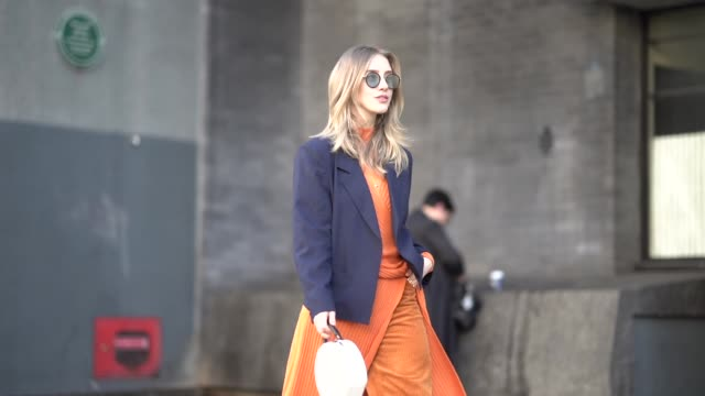 stockvideo's en b-roll-footage met guest wears sunglasses, a blue blazer jacket, orange flare corduroy trousers, an orange wool pullover, a white round bag, during london fashion week... - blazer