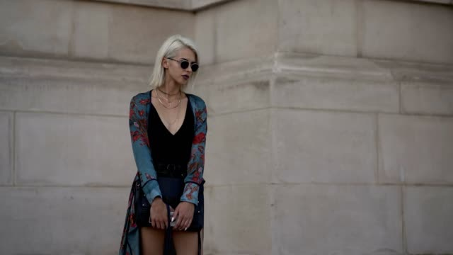 A guest wears sunglasses a blue flower print silk long dress a low neck black top black shorts black shoes outside the Cerruti show during Paris...