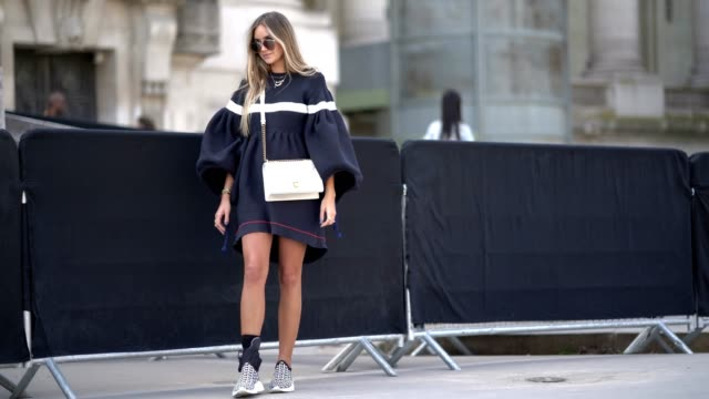 A guest wears sunglasses a blue oversized pull over dress a white dior bag sneakers outside the Ralph Russo show during Paris Fashion Week Haute...