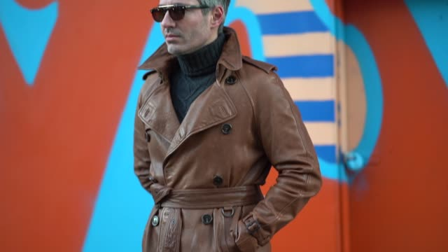 guest wears sunglasses, a brown leather coat, a turtleneck, during london fashion week men's january 2018 on january 07, 2018 in london, england. - london fashion week点の映像素材/bロール