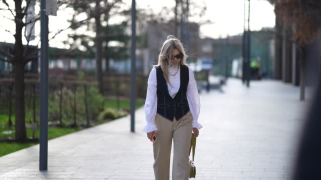 a guest wears sunglasses a chain necklace a white ruffled top a blue sleeveless jacket beige pants a khaki crocodile pattern ratius and motus bag... - sleeveless top stock videos & royalty-free footage