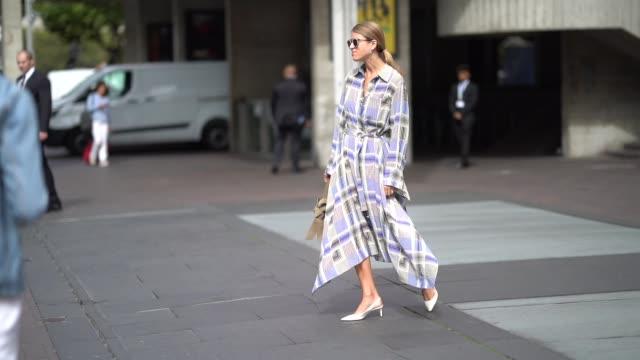 vídeos de stock e filmes b-roll de guest wears sunglasses, a checked purple dress, white shoes, during london fashion week september 2018 on september 16, 2018 in london, england. - dress
