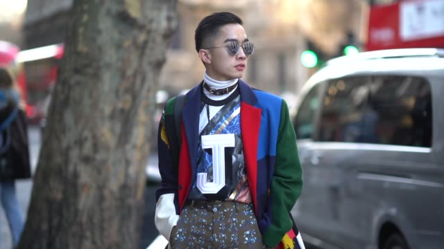 A guest wears sunglasses a colorful outfit during London Fashion Week Men's January 2018 on January 07 2018 in London England