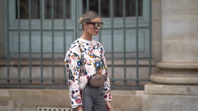 A guest wears sunglasses a colorful print sweater a chocolate brown Gucci beltbag a grey princeofwales flare pants with red stripe on the side white...