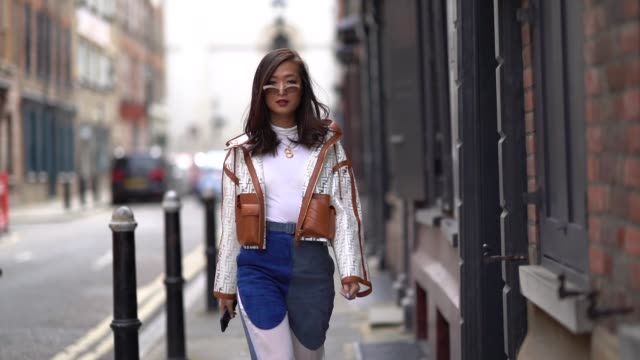 guest wears sunglasses, a fendi plastic monogram jacket with brown leather, blue and white flare pants, a golden necklace, during london fashion week... - jacka bildbanksvideor och videomaterial från bakom kulisserna