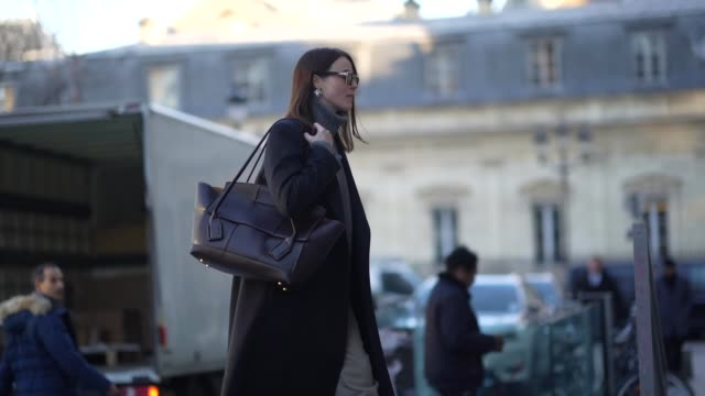 stockvideo's en b-roll-footage met a guest wears sunglasses a gray wool turtleneck pullover earrings a long coat a black leather bag black leather boots outside viktor rolf during... - coltrui