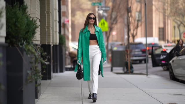 a guest wears sunglasses a green turquoise shiny pvc long coat black bras white pants black shiny shoes a bag during new york fashion week fall... - pants stock videos & royalty-free footage