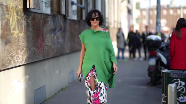 guest wears sunglasses, a green wool ripped pullover, a colored dress with several printed features, green pointy shoes outside marni, during milan... - fashion week stock videos & royalty-free footage