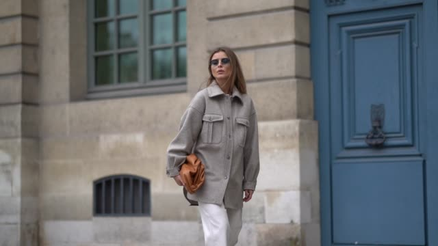 a guest wears sunglasses a light grey boiled wool jacket a tancolor puff bag white pants black and creamcolor pointy boots outside guy laroche during... - grey jacket stock videos and b-roll footage