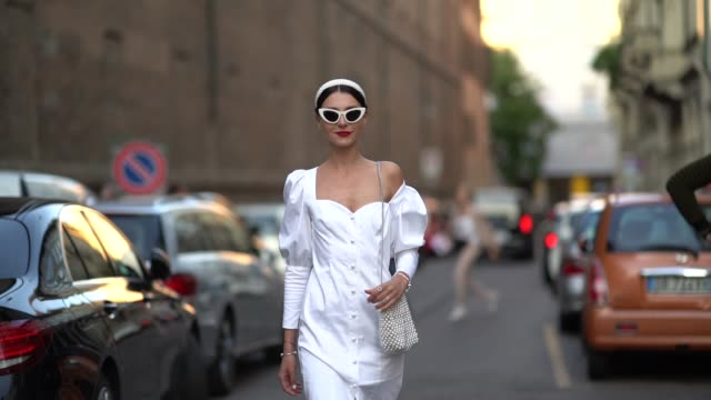 guest wears sunglasses, a one-shoulder ruffled white dress with buttons, a beaded bag, a headband, outside the bottega veneta show during milan... - street style stock videos & royalty-free footage