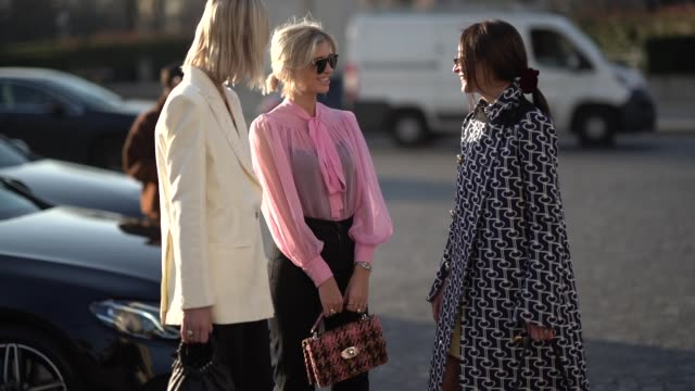 A guest wears sunglasses a pink blouse with a bow a brown and orange tweed handbag a guest wears sunglasses a navy blue and white geometrical design...