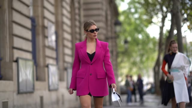 stockvideo's en b-roll-footage met guest wears sunglasses, a pink long blazer jacket dress, a white bag, white shoes, outside redemption, during paris fashion week - womenswear spring... - blazer