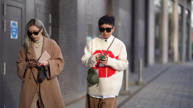 a guest wears sunglasses a turtleneck pullover a brown long wool coat red leather pointy high boots declan chan wears sunglasses a white oversized... - brown stock videos & royalty-free footage