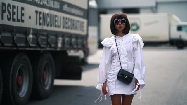 stockvideo's en b-roll-footage met guest wears sunglasses, a white dress, a chanel bag, white sneakers , during feeric fashion week 2018, on july 20, 2018 in sibiu, romania. - witte jurk