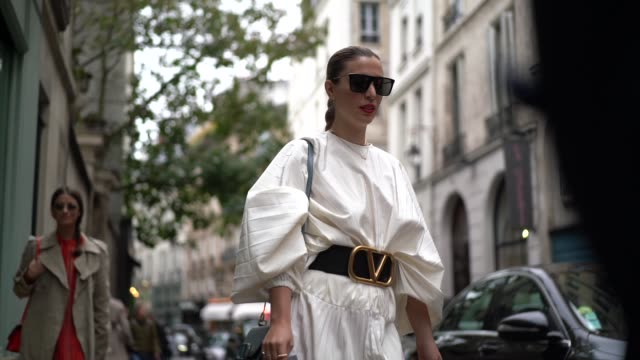 stockvideo's en b-roll-footage met guest wears sunglasses, a white pleated dress, a valentino large belt with logo, outside thom browne, during paris fashion week - womenswear spring... - modeweek