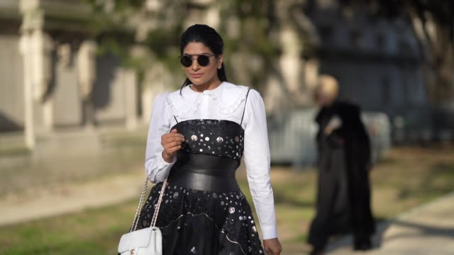 guest wears sunglasses, a white ruffled top, a black lace mesh dress with shiny inserts, a black leather corset, a white chanel bag, black leather... - paris fashion week - haute couture spring/summer 2020点の映像素材/bロール
