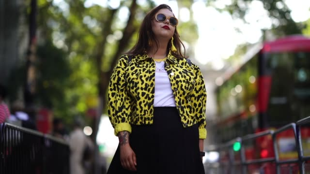 vídeos de stock e filmes b-roll de a guest wears sunglasses a yellow and black printed jacket a white top a black skirt yellow sneaker shoes during london fashion week september 2018... - saia