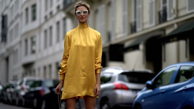 stockvideo's en b-roll-footage met guest wears sunglasses, a yellow dress, a yellow valentino rockstud bag, yellow heels shoes, outside the valentino show, during paris fashion week -... - geel