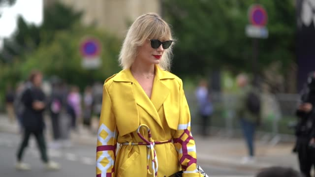 A guest wears sunglasses a yellow trenchcoat with red and white geometric prints a black patent leather bagoutside Lanvin during Paris Fashion Week...