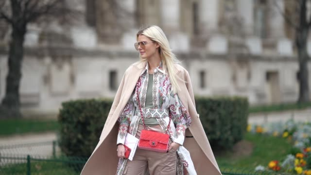A guest wears sunglasses an almondgreen top a beige coat a colorful flowing tunic an orange Chanel bagbeige pants beige pointy laceup boots outside...
