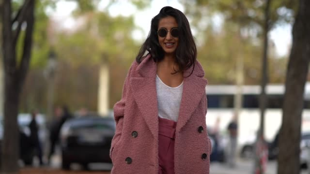 stockvideo's en b-roll-footage met a guest wears sunglasses an old rose coat a white top dark rose pants print grey shoes outside the rochas show during paris fashion week womenswear... - jas