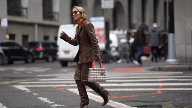 guest wears sunglasses, an orange turtleneck pullover, a checkered lady dior bag with an orange handle, brown snake pattern printed high heeled... - ニューヨークファッションウィーク点の映像素材/bロール