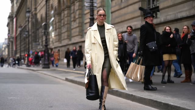 guest wears sunglasses, earrings, a beige trench coat, a front-split khaki leather dress, a black bag with a brown coin purse, black leather and... - トレンチコート点の映像素材/bロール