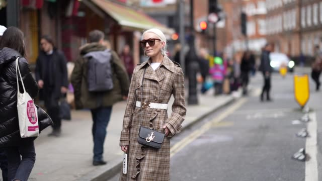a guest wears sunglasses earrings a brown checked trench coat a belt a jw anderson bag white flare pants during london fashion week february 2020 on... - brown stock videos & royalty-free footage