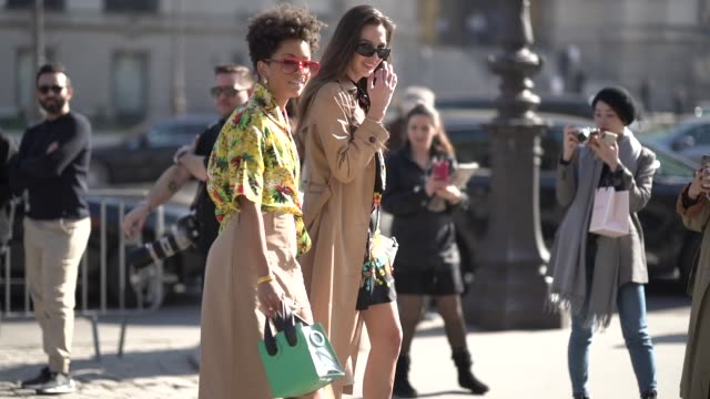 vidéos et rushes de guest wears sunglasses, earrings, a hawaiian shirt, a beige front-split skirt with eyelets, a green bag ; estelle chemouny wears sunglasses, a camel... - beige