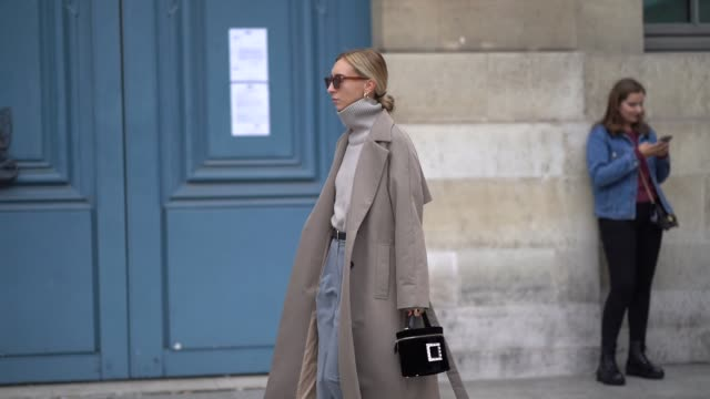 a guest wears sunglasses earrings a light grey turtleneck a beige trench coat a black bag greyblue pants a black belt black mules outside guy laroche... - turtleneck stock videos & royalty-free footage