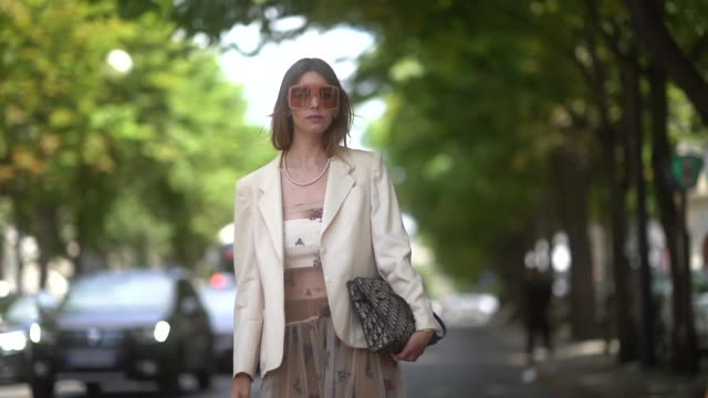 A guest wears sunglasses earrings a necklace a white jacket a Dior monogram bag white transparent shoes a fishnet embroidered ruffled long dress over...